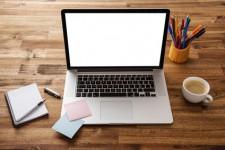 Notebook aufgeklappt auf Holztisch